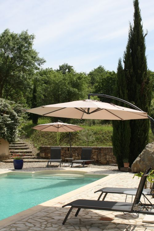 Zwembad voorzien van ligstoelen en parasols